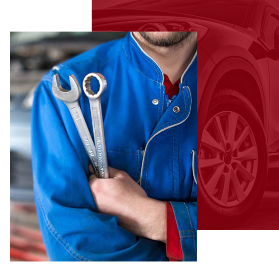 Mechanic in blue holding wrenches